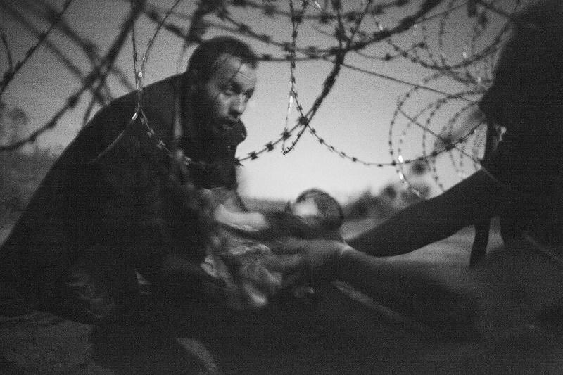 couple réfugié tentant de faire passer leur bébé sous une clôture barbelée
